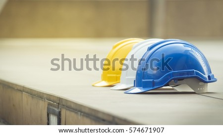 white, yellow and blue hard safety helmet hat for safety project of workman as engineer or worker, on concrete floor on city Royalty-Free Stock Photo #574671907