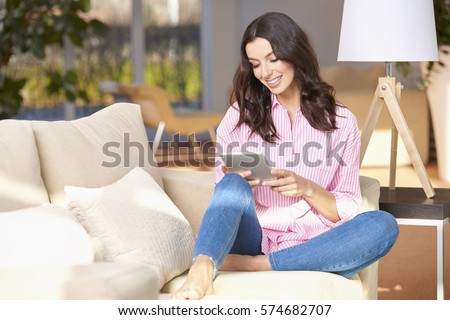 Full length shot of a young woman using her digital tablet while sitting in her cozy home.  #574682707