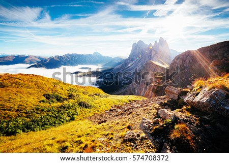 Aerial view of the alpine valley in sunlight. Great and gorgeous morning scene. Location place Puez-Odle National Park, Gardena, Seceda peak, Geisler Dolomiti group. Tyrol, Italy, Europe. Beauty world #574708372