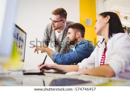 Young colleagues discussing photographs at creative office