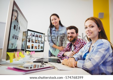 Portrait of smiling graphic designers at desk in creative office #574768399