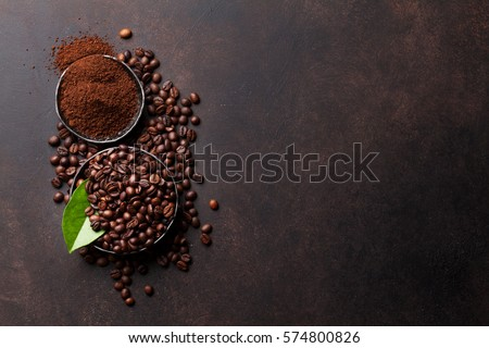 Coffee beans and ground powder on stone background. Top view with copy space for your text  #574800826
