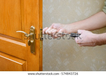 A man is mounting the protection strike of the deadbolt on a door with a classical curved style bronze handle using a screwdriver #574843726