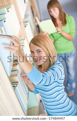 Student in library - two woman choose book from bookshelf #57484447