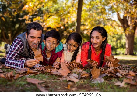 Happy family lying on field at park during autumn #574959106