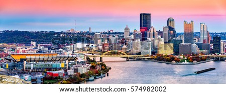 Pittsburgh, Pennsylvania skyline at sunset and the city football stadium across Allegheny river