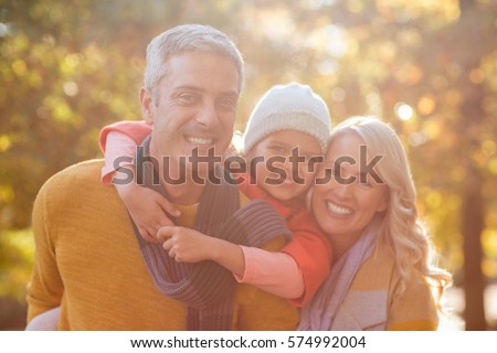 Portrait of happy family against trees at park on sunny day #574992004
