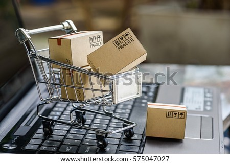 Many paper boxes in a small shopping cart on a laptop keyboard. Concepts about online shopping that consumers can buy things directly from their home or office just using a few clicks via web browser. #575047027