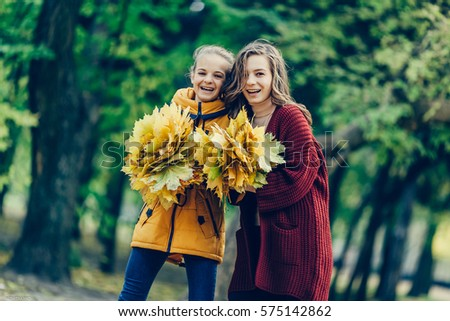 Two sisters hug, with a bunch of leaves in the park.