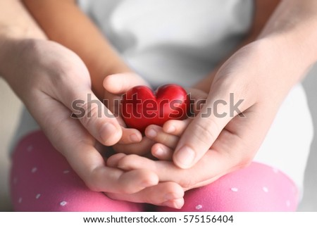 Child and adult person holding small red heart, closeup. Adoption concept #575156404