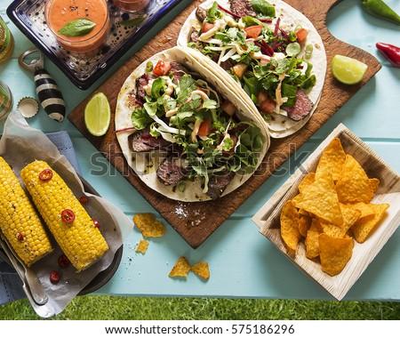 Mexican picnic party outdoor - quesadillas, corn, nachos, gazpacho and beer #575186296