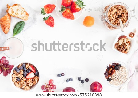 Healthy breakfast with muesli, fruits, berries, nuts on white background. Flat lay, top view, copy space. Royalty-Free Stock Photo #575210398