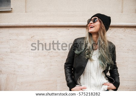 Photo of young pretty lady wearing hat and sunglasses walking on the street. #575218282