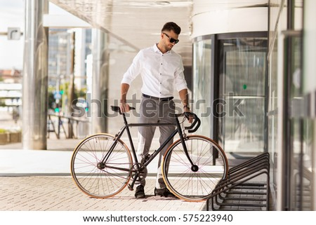 business, lifestyle, transport and people concept - young man parking bicycle on city street Royalty-Free Stock Photo #575223940