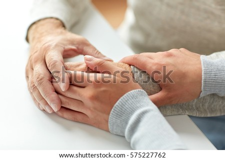 old age, support, charity, care and people concept - close up of senior man and young woman holding hands #575227762