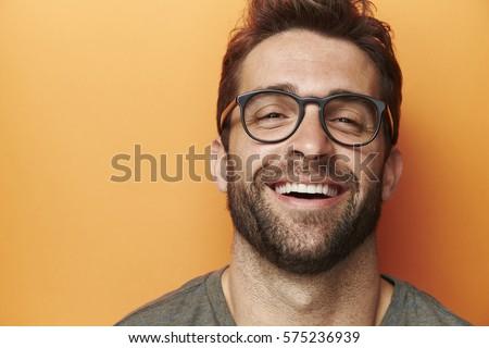 Man laughing in orange studio, close up Royalty-Free Stock Photo #575236939