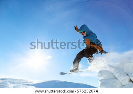 Snowboarder jumping through air with deep blue sky in background #575252074