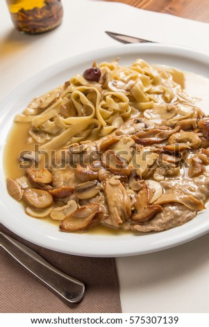 Italian veal scallopini with tagliatelle and mushrooms in rich gravy. #575307139