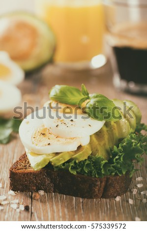 Sandwich with avocado and boiled egg on wooden background, retro toned #575339572