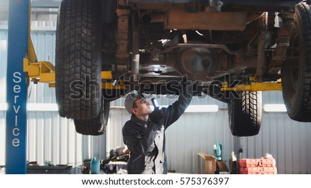 Car service - a mechanic checks the suspension of SUV, wide angle #575376397