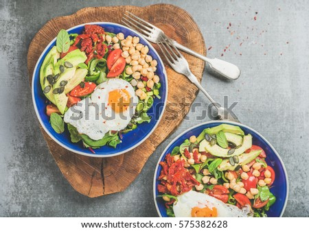Healthy breakfast bowls with fried egg, chickpea sprouts, seeds, vegetables and greens over grey concrete background, top view. Clean eating, dieting, healthy lifestyle, detox, vegetarian food concept #575382628