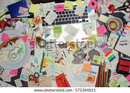Top view on office desk with laptop computer and  notes all around. Overwhelmed with work concept. Royalty-Free Stock Photo #575384821