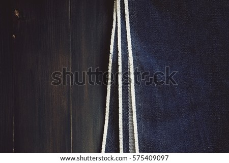 Denim on a brown wooden background. #575409097