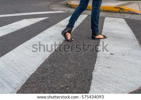 Young woman feet, crossing an urban street. #575434093