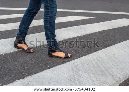 Young woman feet, crossing an urban street. #575434102