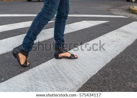 Young woman feet, crossing an urban street. #575434117