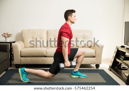 Profile view of a young and fit man doing kneeling lunges with a pair of dumbbells at home #575462254