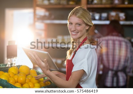 Portrait of smiling staff using digital tablet while checking fruits in organic section of supermarket #575486419