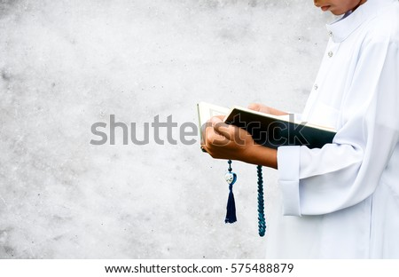 muslim child reading a book on gradient background, in Islam study. Royalty-Free Stock Photo #575488879