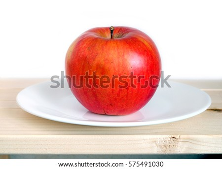Big ripe apple on white plate in wooden shelf on white background front view closeup #575491030