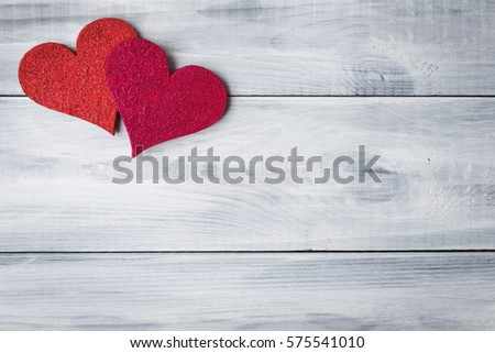 Red hearts over white wooden background with copy space