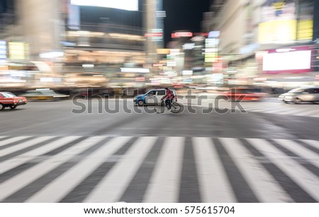 TOKYO, JAPAN - JANUARY 28, 2017: Shibuya District in Tokyo. Famous and busiest intersection in the world, Japan. Shibuya Crossing. Blurry Panning Cars and Rider. #575615704