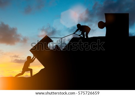 Silhouette team business helps to systematically patience hard work and the pressure to reach the finish line Motivate employee growth concept jigsaw over blurred natural Royalty-Free Stock Photo #575726659
