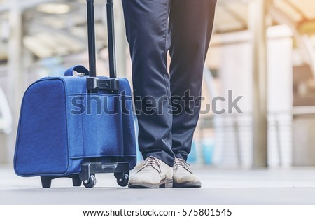 Businessman,backpacker carrying suitcase while walking through a passenger boarding bridge,A business traveler with suitcase,male legs closeup. stylish man with a suitcase standing at the Street  #575801545