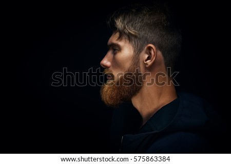 Close-up image of serious brutal bearded man on dark background Confident and dramatic concept Royalty-Free Stock Photo #575863384
