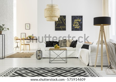 Bright room with white sofa, table, pattern carpet and lamp #575914609