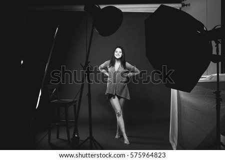 Beautiful young model posing in the atelier. Photos from fashion photoshoot. Dark room and silhouettes studio lights.