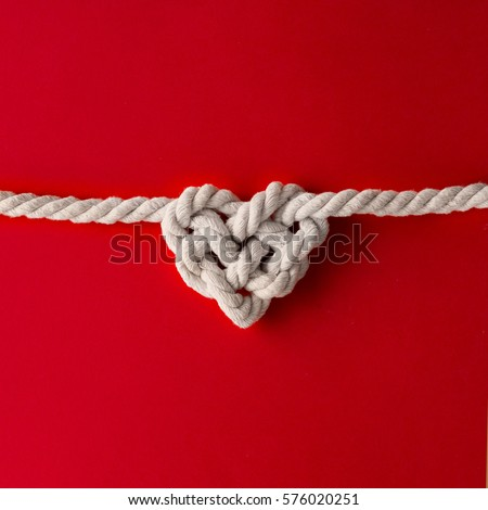 White rope in heart shape knot on red background. Love concept. Flat lay. Royalty-Free Stock Photo #576020251