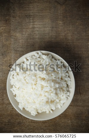Cooked rice isolated on wooden background #576065725