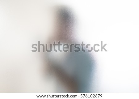 The shadow of an unknown man through the glass using a mobile phone and documents. #576102679