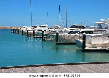 Boats and yachts in a marina. Royalty-Free Stock Photo #576109324