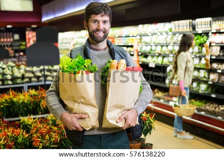 Portrait of smiling man holding a grocery bag in organic section of supermarket #576138220