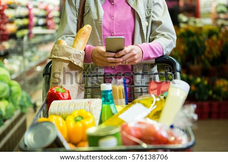 Woman using mobile phone while shopping in supermarket #576138706