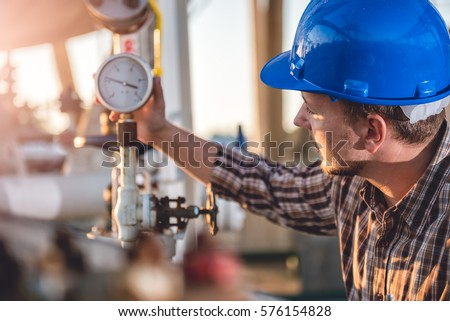 Man checking manometer in natural gas factory Royalty-Free Stock Photo #576154828