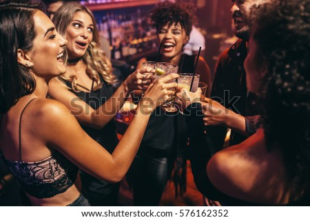 Group of friends partying in a nightclub and toasting drinks. Happy young people with cocktails at pub. Royalty-Free Stock Photo #576162352