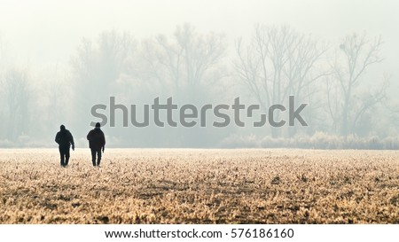 Panorama with silhouette of the two hunters, photographer, hikers or tourists on the field at sunrise. Group of people going up in the early morning in a rural field through the grass during hunting.